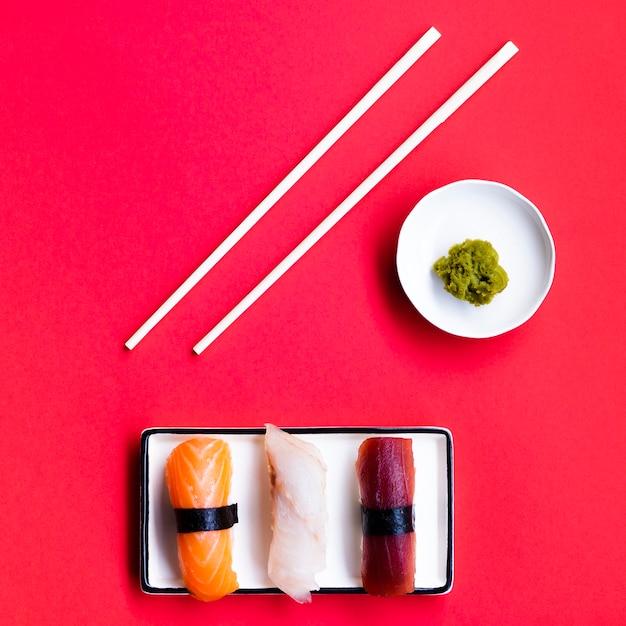Plato de sushi con palitos de wasabi y chop sobre un fondo rojo. Foto gratis
