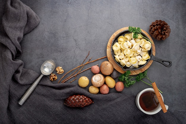 Plato de tortellini y champiñones sobre un fondo gris Foto gratis