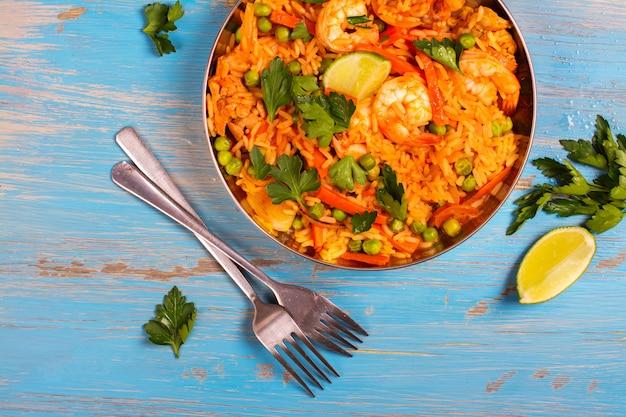 Plato tradicional de paella española con mariscos, guisantes, arroz y pollo Foto Premium