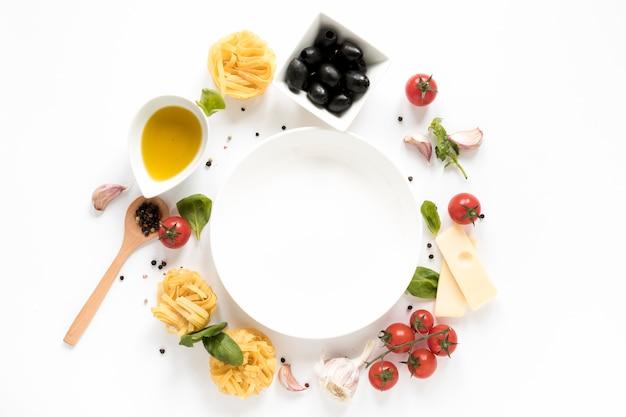 Plato vacío rodeado de ingrediente de pasta italiana y cuchara de madera aislada sobre fondo blanco Foto Premium
