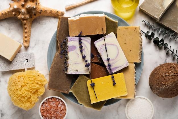 Plato de vista superior con jabón y productos cosméticos. Foto gratis