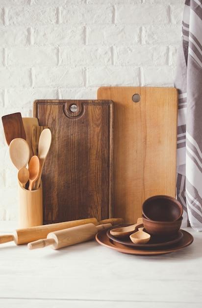Platos de cerámica, cubiertos de madera o bambú, tablas de cortar y toalla en el interior de la cocina. Foto Premium