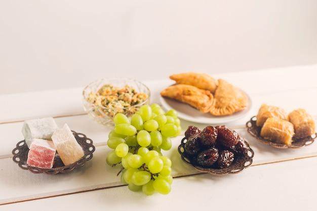 Platos orientales y uvas sobre mesa. Foto gratis
