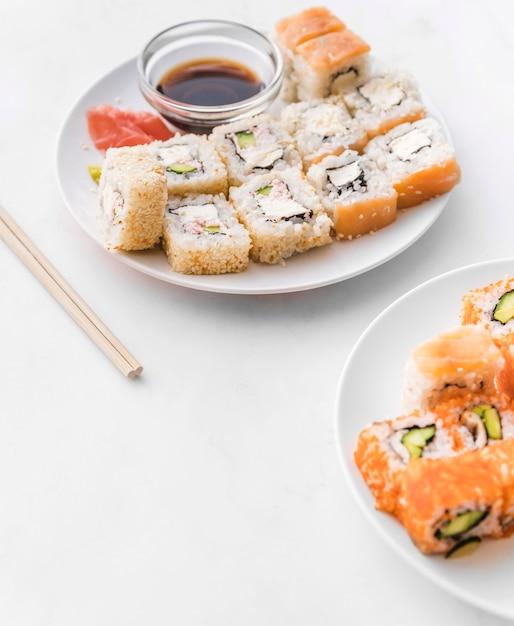 Platos de sushi en ángulo con salsa de soja Foto gratis