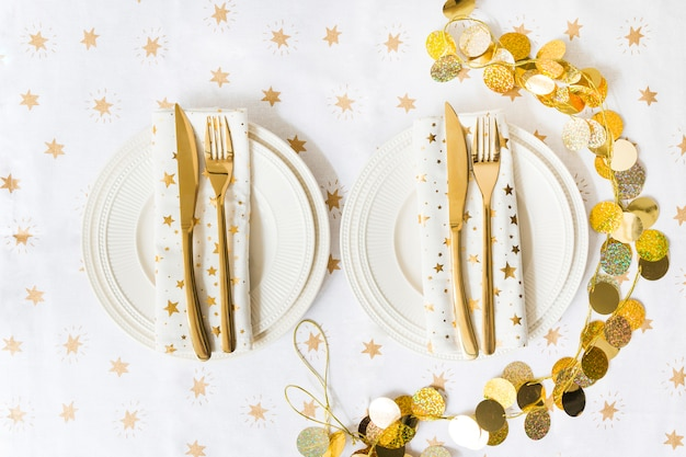 Platos con tenedor y cuchillo en mesa de luz. Foto gratis