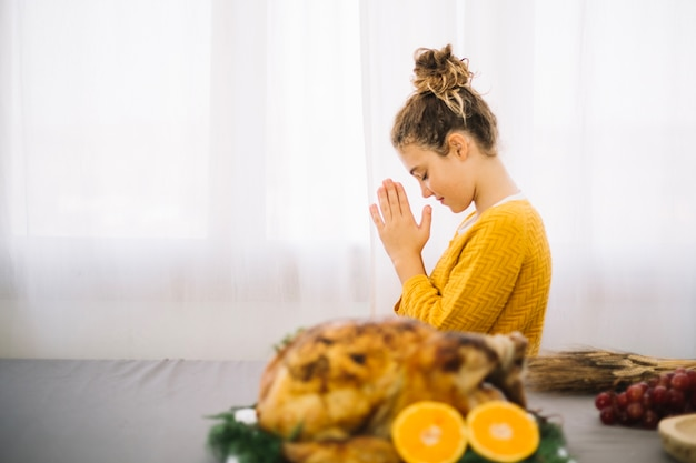 Platos de thanksgiving con vista lateral de mujer rezando Foto gratis