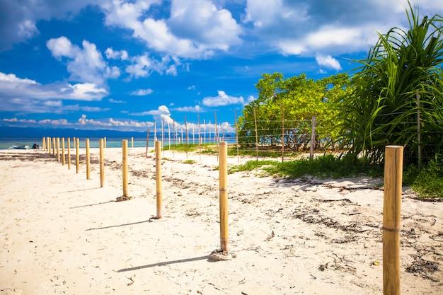 Playa blanca perfecta con agua turquesa y una pequeña valla en la isla desierta Foto Premium