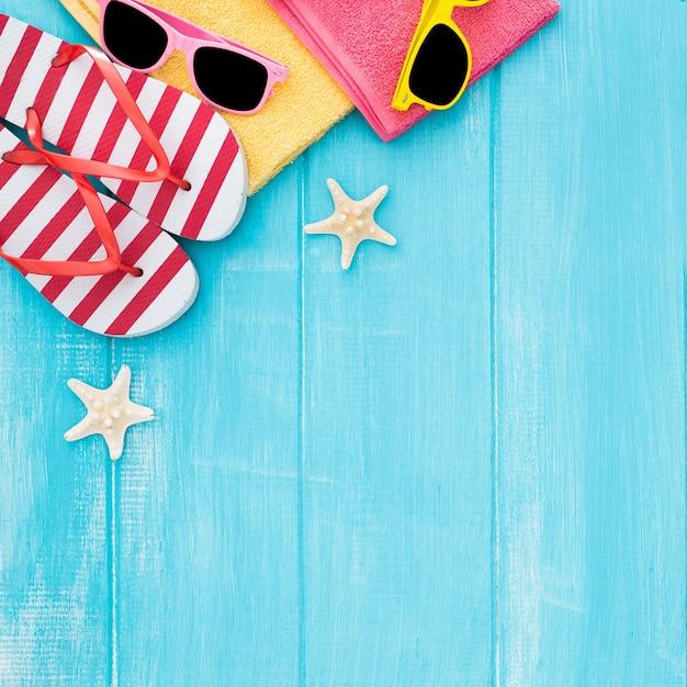 Playa de verano para tomar el sol fondo de madera, gafas de sol, chanclas, espacio de copia Foto gratis