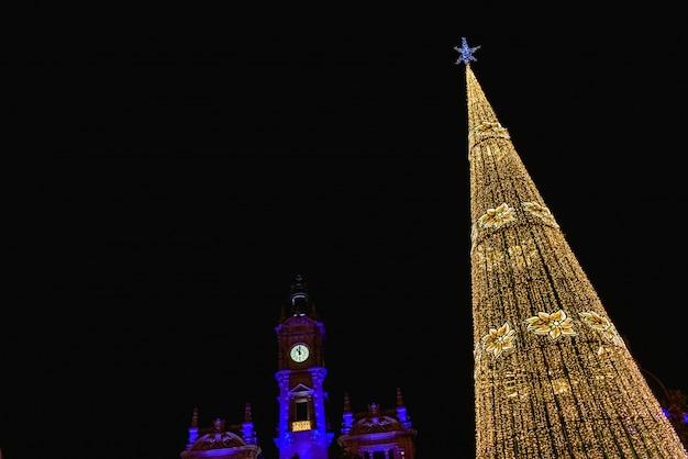 La plaza modernisme en valencia, españa, al anochecer, iluminada por un brillante árbol de navidad y edificio del ayuntamiento de la ciudad, al fondo. Foto Premium