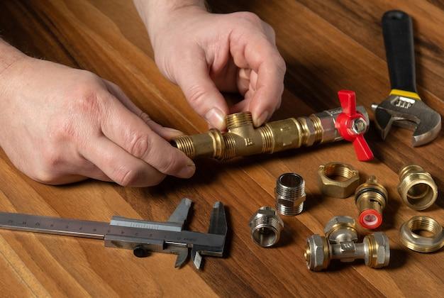 El plomero conecta los accesorios de latón mientras repara el equipo. Foto Premium