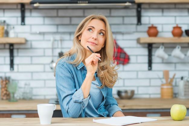 Pluma de tenencia de la mujer joven a disposición que piensa mientras que escribe en el cuaderno Foto gratis