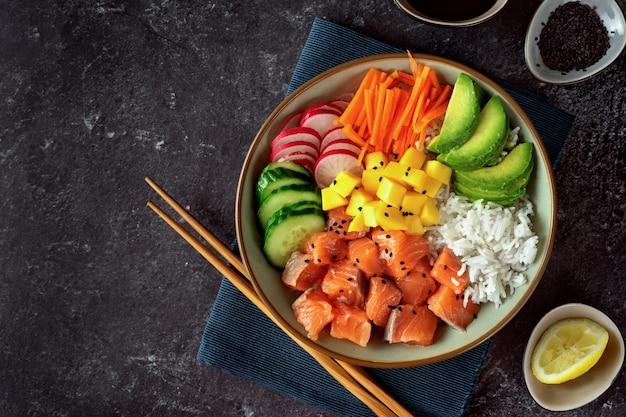 Poke bowl de salmón con aguacate, arroz, zanahorias en vinagre y pepino Foto Premium