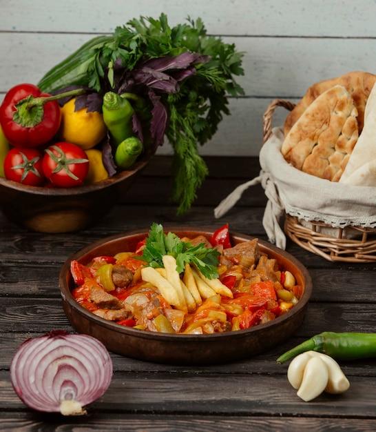 Pollo asado con pimientos, cebolla y tomate en una sartén de cerámica Foto gratis