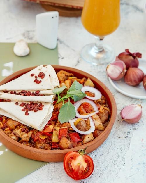 Pollo asado y verduras en una sartén de cerámica Foto gratis