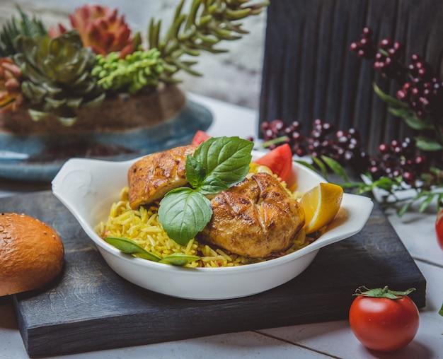 Pollo frito con arroz, tomate y limón Foto gratis