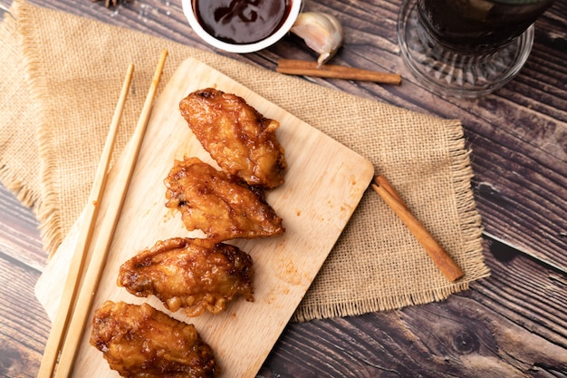 Pollo frito asado coreano caliente y picante en la tabla de cortar de madera Foto Premium