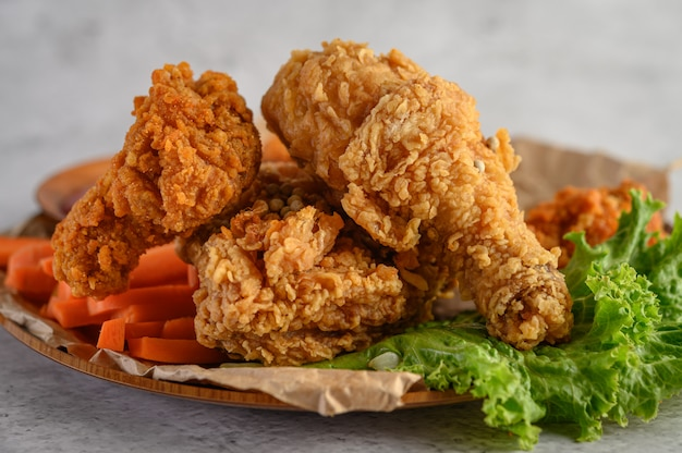 Pollo frito crujiente en un plato con ensalada y zanahoria Foto gratis