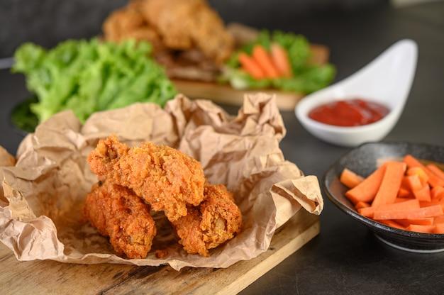 Pollo frito crujiente sobre una tabla de cortar con salsa de tomate y zanahoria Foto gratis