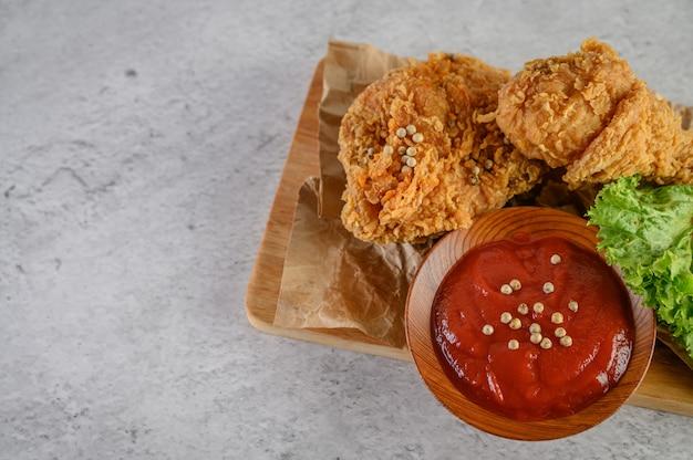 Pollo frito crujiente sobre una tabla de cortar con salsa de tomate Foto gratis