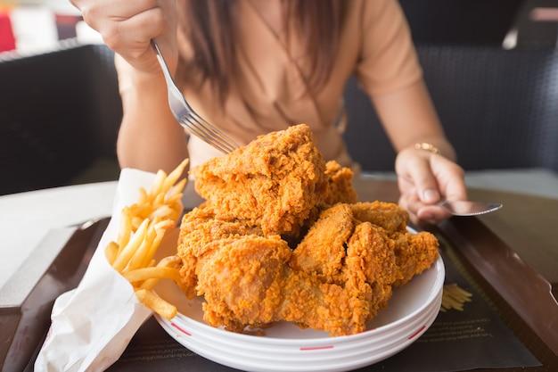 Pollo frito en mano de mujer joven seleccionar el foco Foto Premium