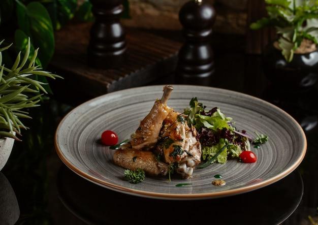 Pollo salteado en plato de cerámica azul con ensalada Foto gratis