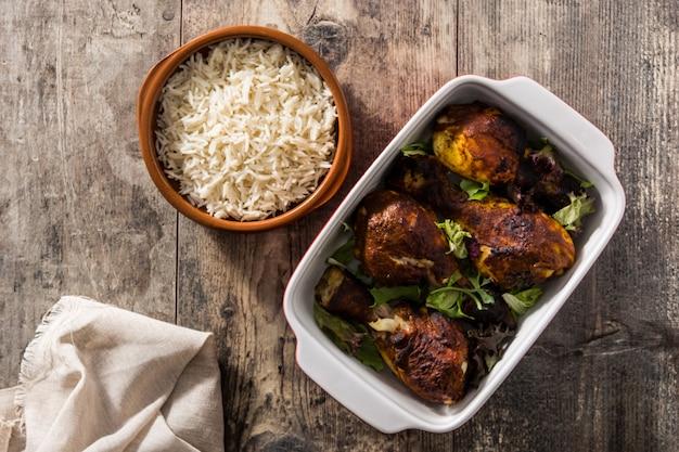 Pollo tandoori asado con arroz basmati en la mesa de madera. vista superior. Foto Premium