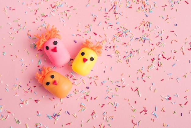 Pollos hechos de cajas de juguetes de huevo con chispitas de colores Foto gratis
