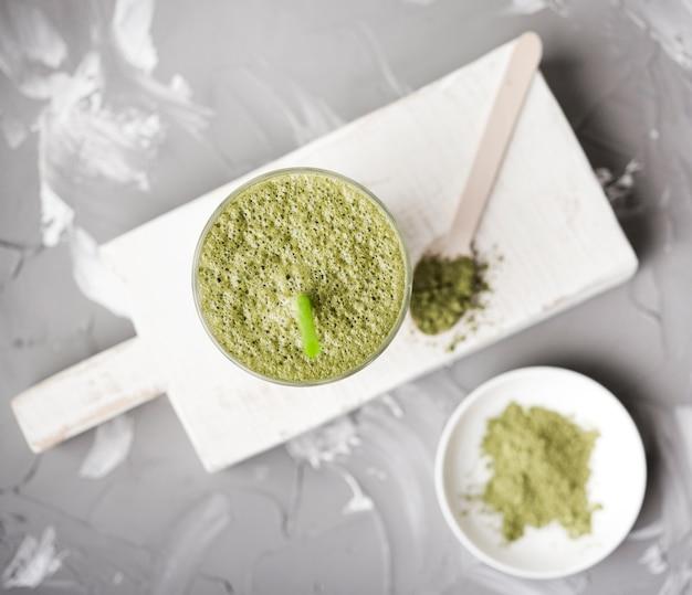 Polvo verde y pasta sobre tabla de madera Foto gratis