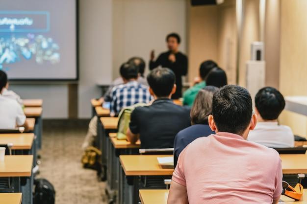 Ponente en el escenario frente a la sala con vista posterior de la audiencia en acción puesta Foto Premium