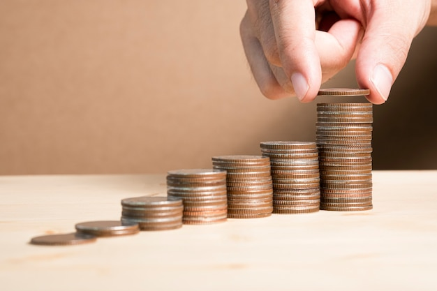 Poner a mano monedas apiladas para ahorrar en el futuro y financiar la inversión del valor de las acciones. Foto Premium