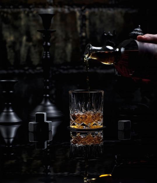 Poner un vaso de whisky escocés mezclado bien Foto gratis