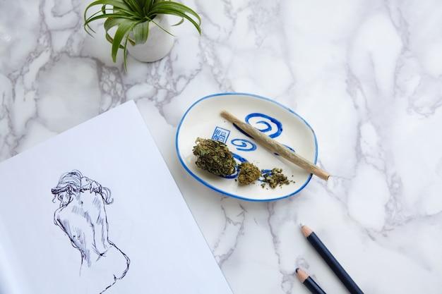 Porro de marihuana thc cbd y flores en cenicero con ilustración desnuda en el bloc de dibujo Foto gratis