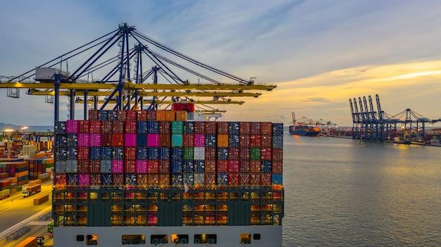 Portacontenedores de carga y descarga en el puerto de aguas profundas al atardecer, vista aérea de logística de negocios de importación y exportación Foto Premium