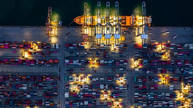 Portacontenedores trabajando por la noche, logística de importación y exportación de negocios. Foto Premium