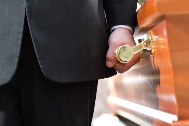 Portador de ataúd llevando ataúd en el funeral Foto Premium