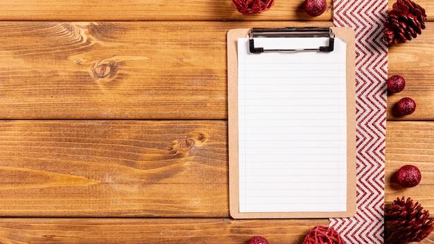 Portapapeles y adornos navideños en mesa de madera Foto gratis
