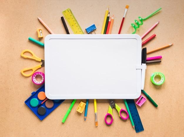 Portapapeles blanco y estacionario brillante en la mesa Foto gratis