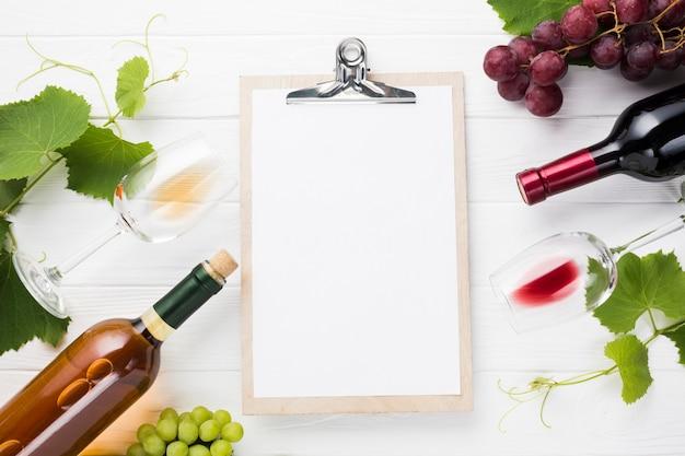 Portapapeles maqueta rodeada de botellas de vino. Foto gratis