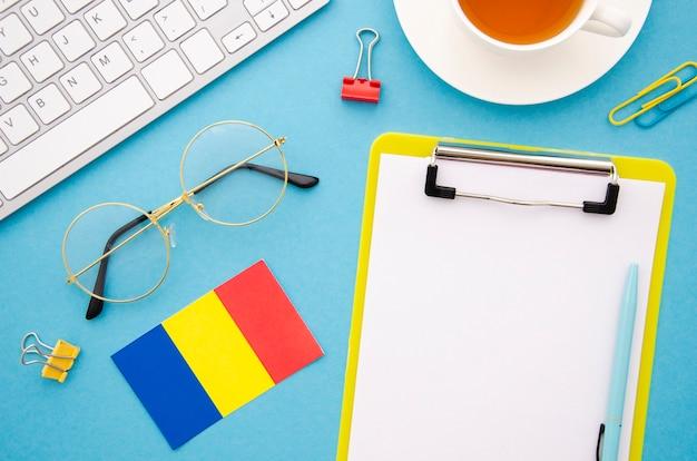 Portapapeles vacío junto a la bandera rumana Foto gratis