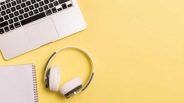Portátil y auriculares sobre fondo amarillo Foto gratis