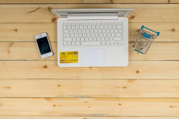 El portátil blanco con teléfono inteligente, tarjeta de crédito y el modelo de carro de compras en el fondo de la mesa de madera. compras de comercio electrónico. Foto Premium