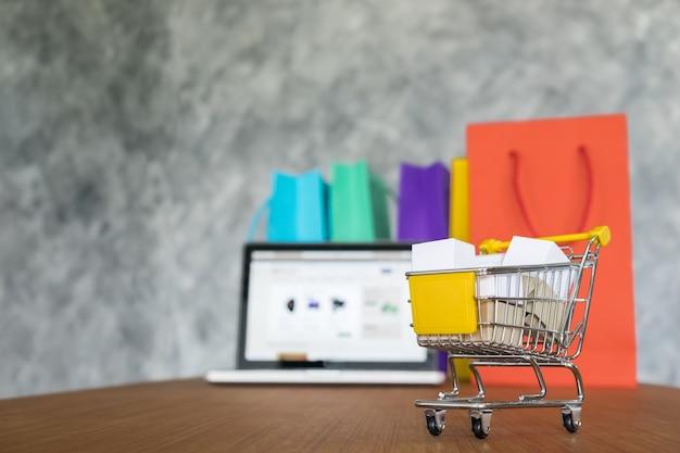 Portátil y bolsas de la compra, concepto de compras en línea Foto gratis