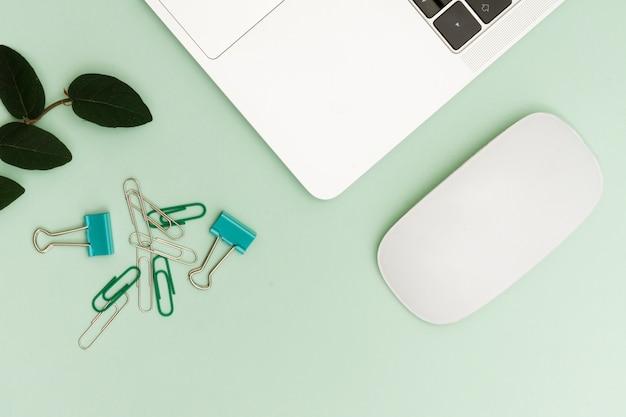 Portátil y clips con planta en escritorio en espacio de trabajo Foto gratis