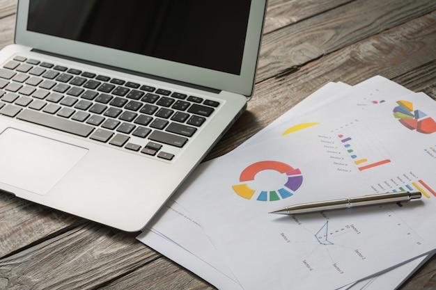 Portátil con documentos de negocios coloridos Foto gratis