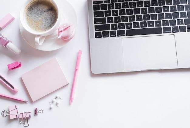 Portátil gris con papelería rosa Foto Premium