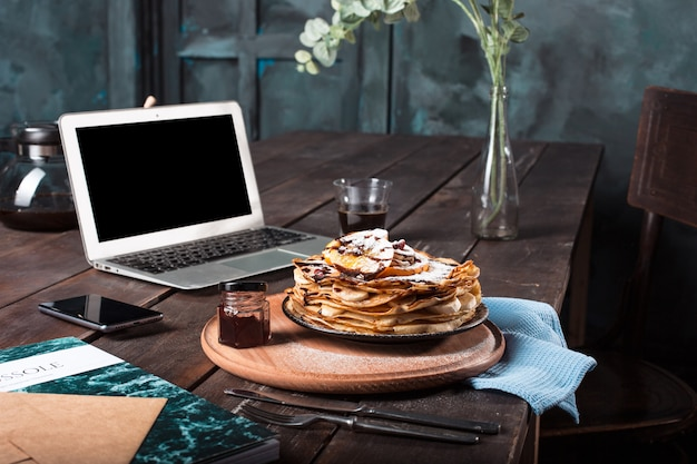 Portátil y panqueques con jugo. desayuno saludable Foto gratis