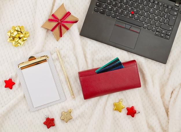 Portátil, tarjetas de crédito, monedero y decoración navideña. compras navideñas en línea, compra de regalos Foto Premium