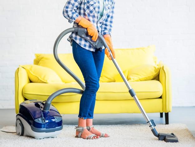 Portero de limpieza de alfombras con aspiradora delante de un sofá amarillo Foto gratis