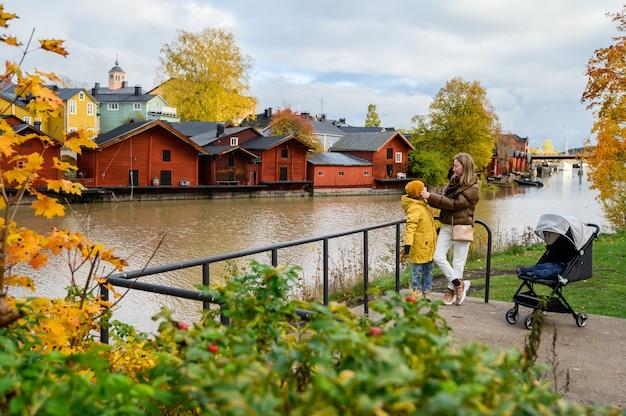 Porvoo, finlandia, madre e hijo en la orilla del río. en el fondo de viejas casas rojas graneros Foto Premium