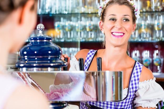 Posadero en pub bávaro con clientes. Foto Premium